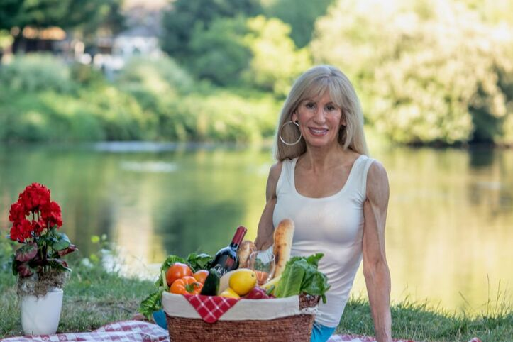 Jeannie Brown, certified health coach, personal trainer, weight loss, habit change and nutrition expert waits to talk with you, next to a river in a park in front of a healthy picnic basket.