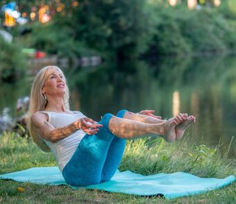 Certified Health and fitness coach, nutrition, lifestyle and weight loss expert Jeannie Brown doing a yoga pose in a park